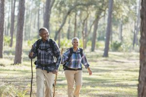 Older African American couple hiking through the woods