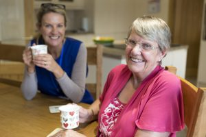 senior and caregiver drinking coffee together