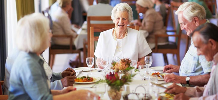 seniors having dinner together in a community dining room