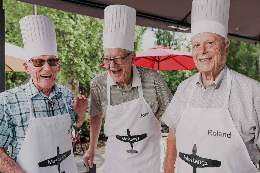 seniors outside wearing aprons cooking