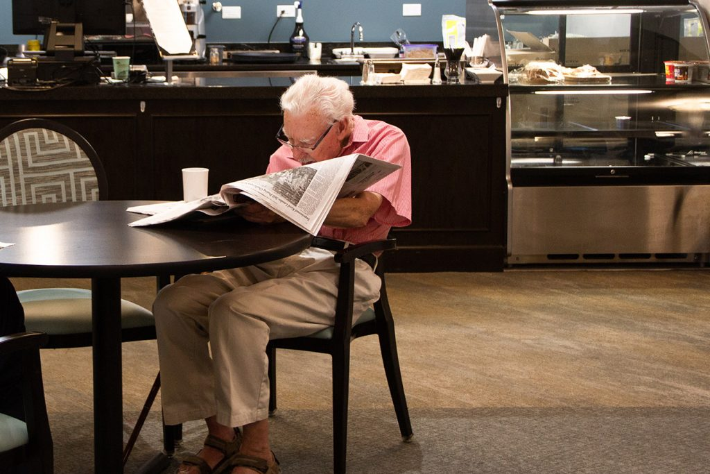 senior reading the newspaper while enjoying a cup of coffee at the cafe of a senior living community