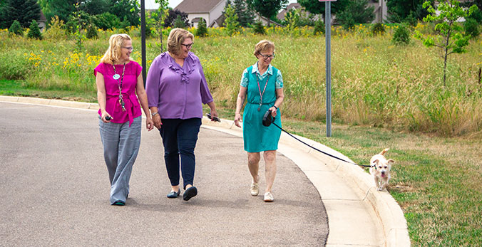 StoryPoint resident and team members walking pets around the senior living community
