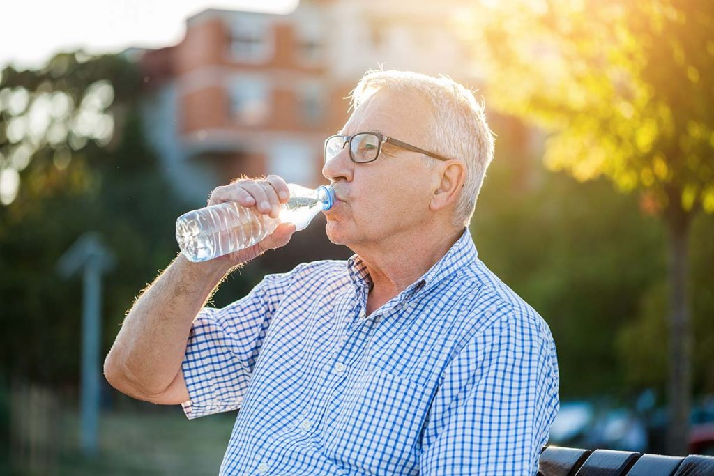 Elderly man enjoying the summer sun while staying hydrated by tracking his water intake.